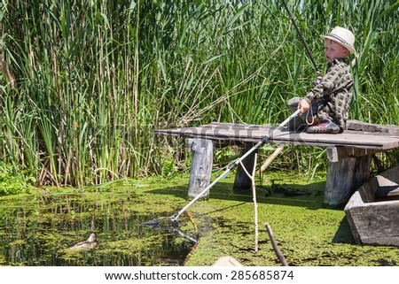 Young fisherman pulls in fish landing net bream caught at the bait - stock photo