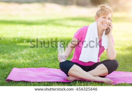 Young Fit Adult Woman Outdoors With Towel And Water Bottle On Yoga Mat Talking Her