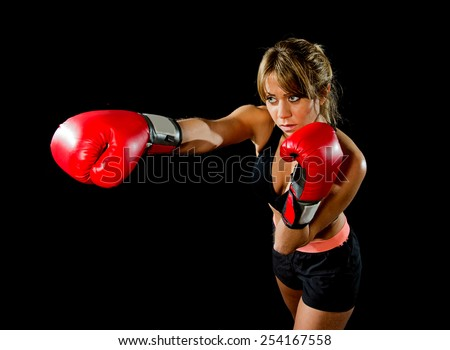 young fit and strong sexy boxer girl with red boxing gloves fighting throwing aggressive punch training workout in gym feeling angry isolated on black background