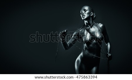 Young fit athletic woman in silver body paint posing with chains. Concept of freedom limitation. Censored version