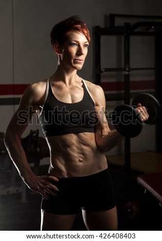 Young fit caucasian female bodybuilder in old school gym