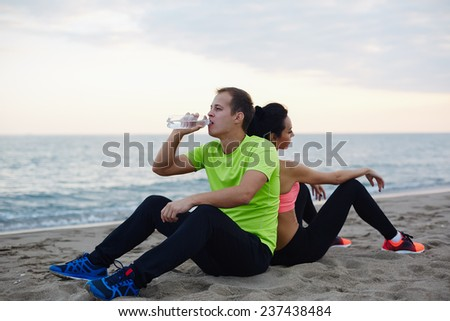 Young fit couple having break after workout outdoors, beautiful caucasian man refreshing with bottle of water exhausted after run, resting couple of two runners sitting on the beach, living healthy - stock photo