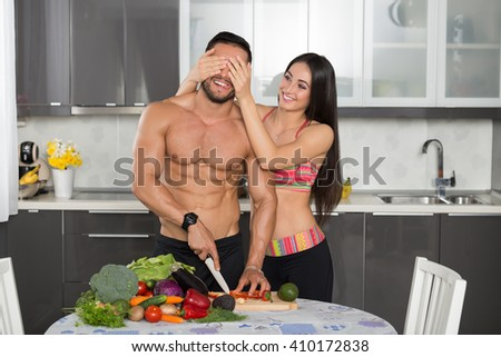 young fit couple in the kitchen, cooking, cutting vegetables, having fun - stock photo