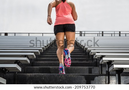 "Young fit female athlete running up bleachers at a stadium to illustrate ""challenge"". - stock photo"