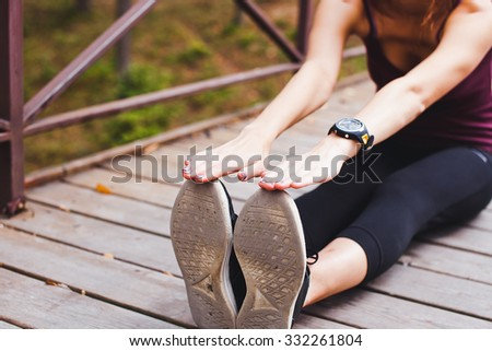 Young fit female athlete warming up and stretching before training sitting on a ground of wooden bridge in park. Smart watch, gps, pulse meter, cardio monitor on wrist. Training outdoors in summer - stock photo