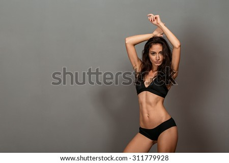 young fit girl in studio on a dark background - stock photo