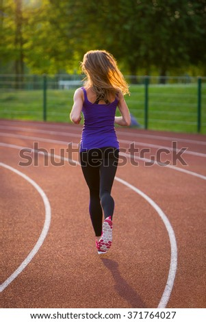 Young fit girl is running on a stadium in a pink shoes and a leggings.