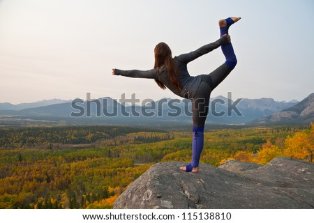 Young fit girl practicing yoga on a cliff over looking the colorful changing autumn leaves - stock photo