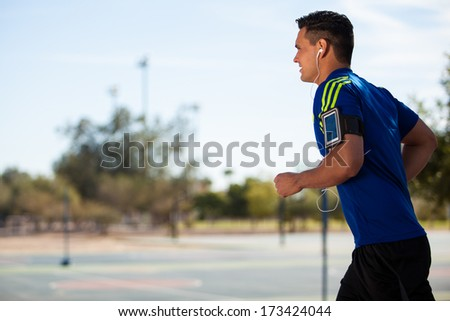 Young fit guy wearing his cell phone with and armband and running on a sunny day - stock photo