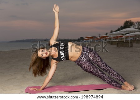 Young fit lady doing yoga on the beach during twilight - stock photo
