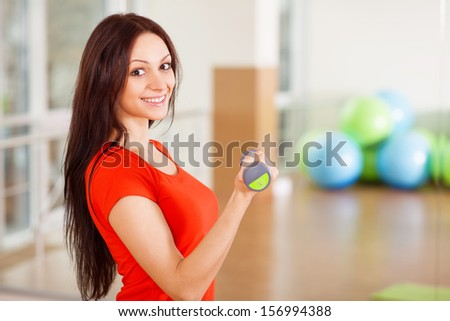 Young fit lady with dumbbells in a gym - stock photo