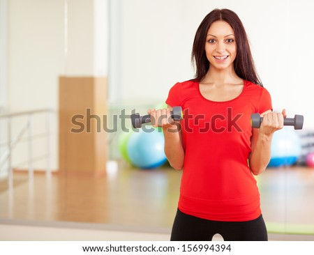 Young fit lady with dumbbells in a gym