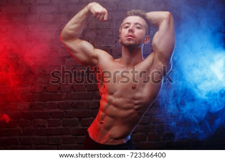 Young fit man bodybuilder with perfect big muscles. Muscled male model posing