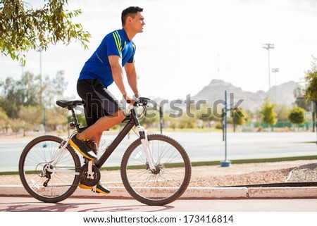 Young fit man during a bike ride on a sunny day - stock photo