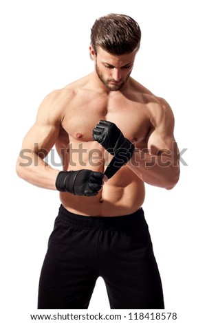 young fit man putting his gloves, preparing for training - stock photo