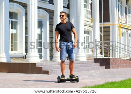 young fit man riding electrical scooter in the city - hoverboard, gyro scooter, smart balance wheel, personal eco transport