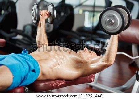 Young fit man working out at bench press with dumbbells - stock photo