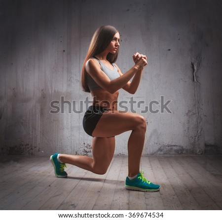 Young fit muscular woman doing lunge in brutal interior - stock photo