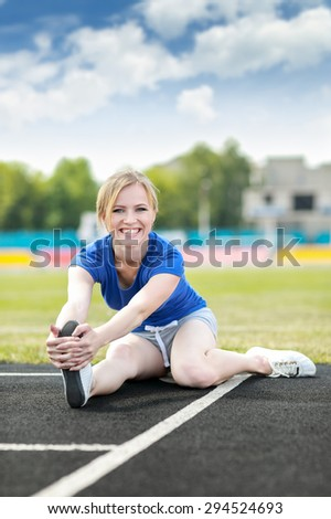 Young fit sports girl stretching out before exercising.