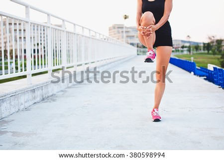Young fit sporty girl runner holds her leg while stretching outdoors at stadium of her university campus. Half-length portrait. No face. Unrecognizable. Copy space - stock photo