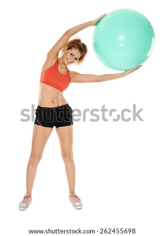 Young fit woman doing aerobics with a gym ball, full length