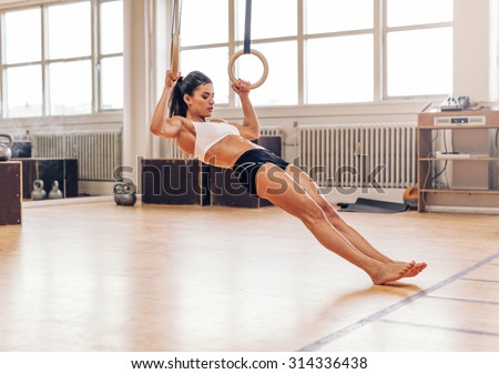 Young fit woman doing pull-ups on gymnastic rings. Muscular young female athlete exercising with rings at gym. - stock photo