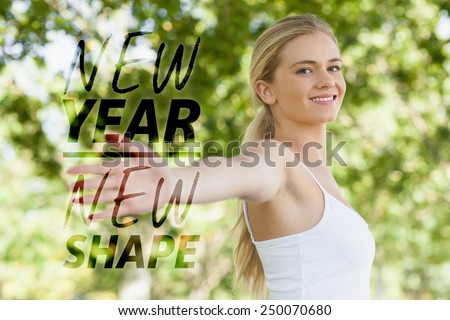 Young fit woman doing yoga in a park spreading her arms against new year new shape - stock photo