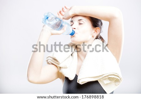 Young fit woman drinking water after fitness training - stock photo