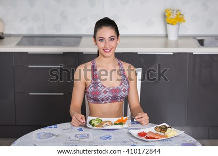 young fit woman in the kitchen, preparing healthy meal: one plate with salmon, mushrooms, potatoes, tomato and red pepper and another with broccoli, chicken grill, carrots and rice