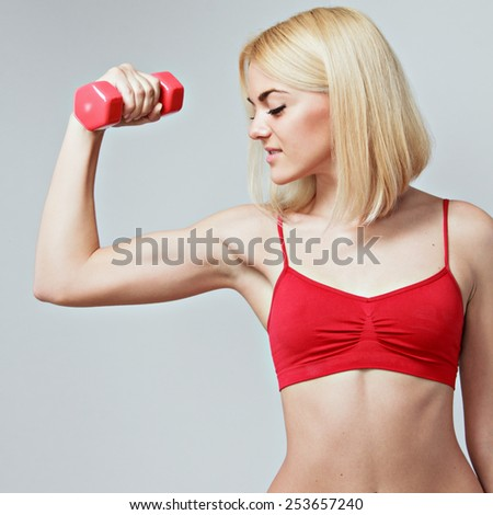 young fit woman lifting dumbbells on grey background