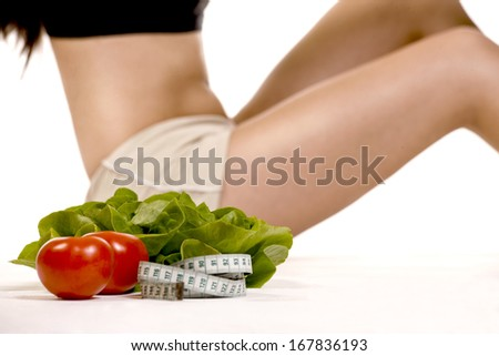 Young fit woman's body with vegetables on white background.