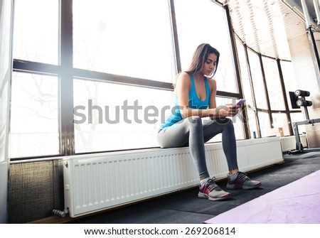 Young fit woman using smartphone at gym - stock photo