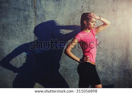 Young fit woman with beautiful figure having rest after workout outdoors at evening, female runner taking break after run while standing against concrete wall with copy pace area for your text content - stock photo