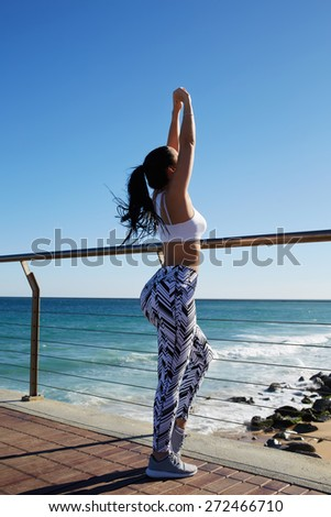 Young fit woman with beautiful figure stretching her arms out before a workout outdoors, female runner warming up before her daily exercise routine on the beach,enjoying nature during fitness training - stock photo