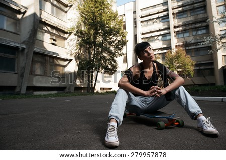 young fit woman with modern haircut sitting on longboard. she is in the shade of building. she wears jeans and singlet. She has tattoos throughout her body. longboard has no prints or aerography - stock photo