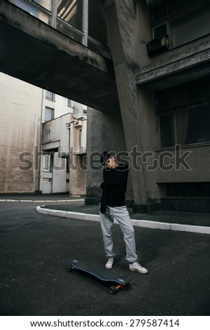 young fit woman with modern haircut standing with longboard. she is in the shade of building. she wears jeans and sweatshirt. She has tattoos throughout her body. longboard has no prints or aerography - stock photo