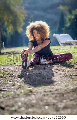 young fitness black woman runner stretching legs after run  - stock photo