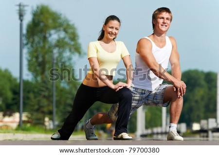 Young fitness couple of man and woman doing physical stretching exercises before jogging sport outdoors - stock photo