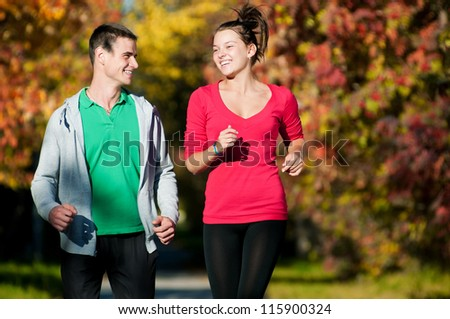 Young fitness couple of man and woman run in park