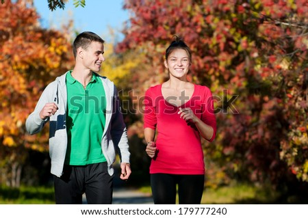 Young fitness couple of man and woman run in park  - stock photo