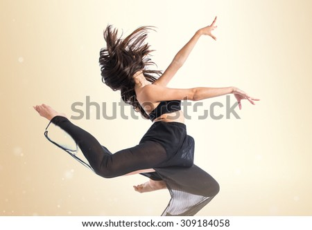 Young fitness female jumping over ocher background