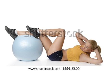 young fitness girl laying on floor doing stretching exercise with a help of big ball - stock photo