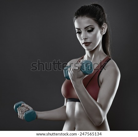 Young fitness girl training with light dumbbells - stock photo