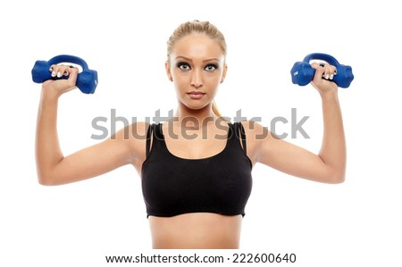 Young fitness girl working out with dumbbells