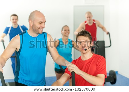 Young fitness instructor lead class treadmill alpinning at the gym - stock photo