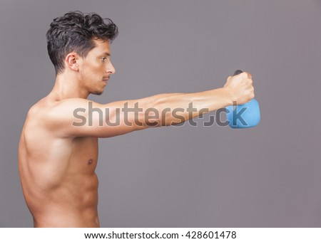 Young fitness male exercise with kettle bell on grey background - stock photo