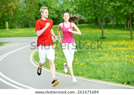 Young fitness man and woman doing jogging run sport outdoors - stock photo