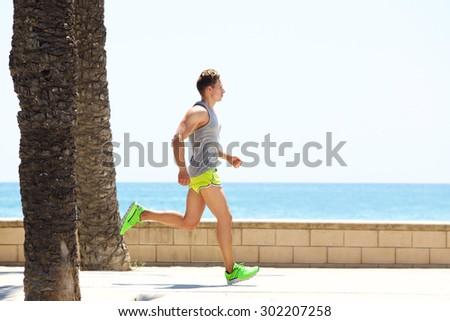 Young fitness man running by the sea side  - stock photo