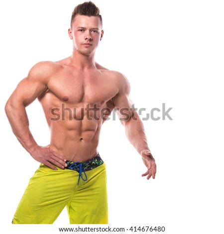 Young fitness model in green shorts over white background