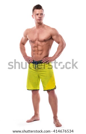 Young fitness model in green shorts over white background - stock photo